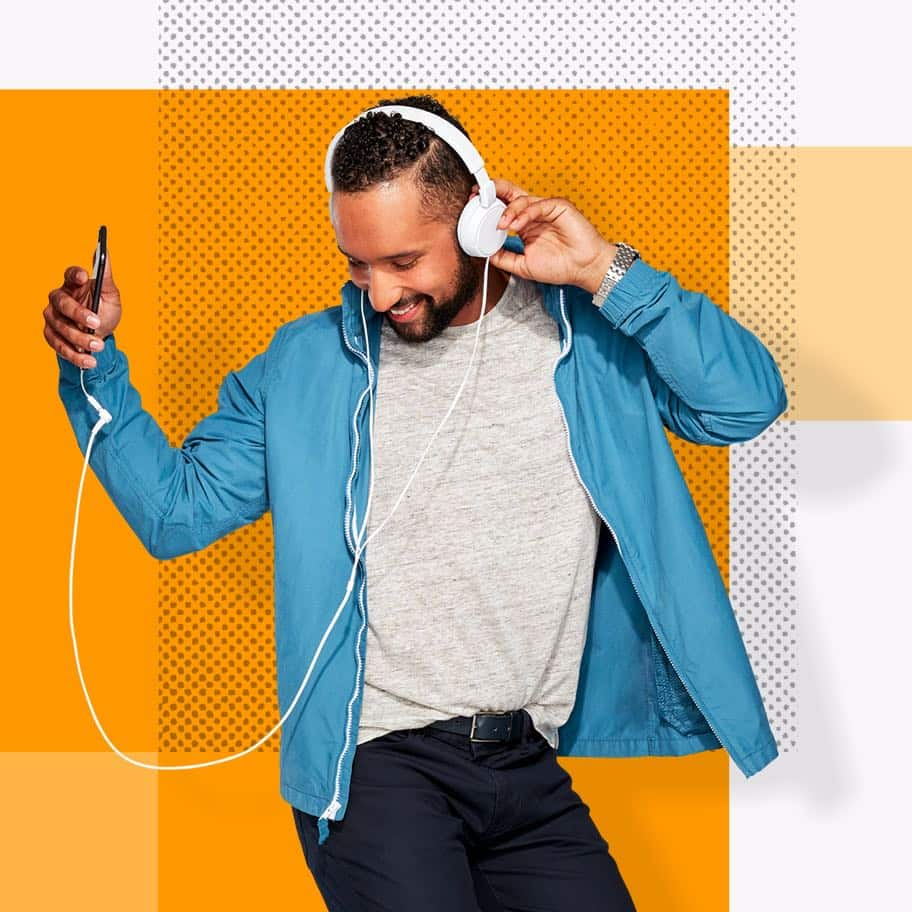 Henry, an Affinity Plus member, listening to headphones dancing, on an orange background