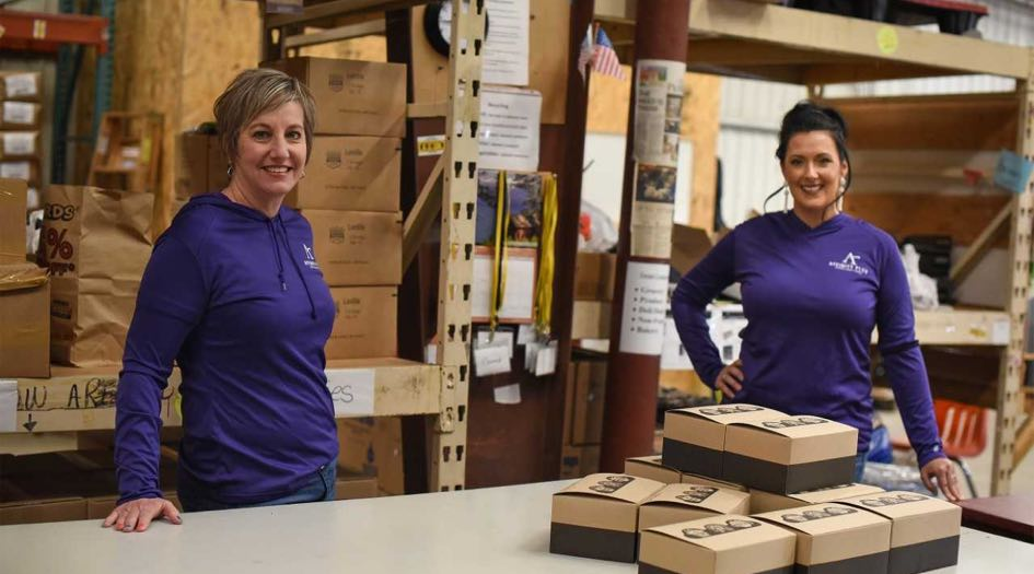 Two smiling women wearing Affinity Plus shirts in warehouse with boxes.