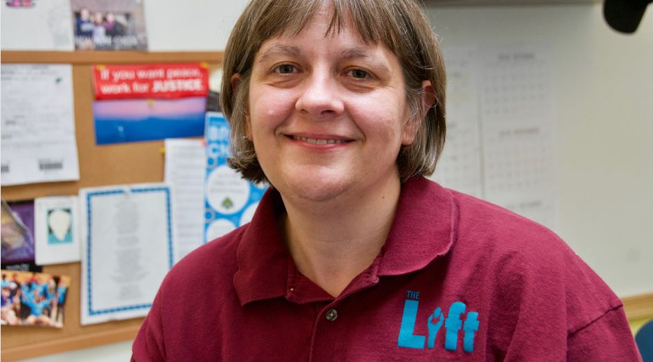 Woman with short brown hair and burgundy polo with logo reading 'Lift Garage'