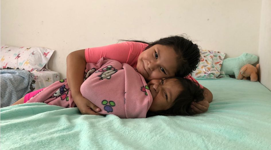 Two smiling young girls hugging on their new bed.