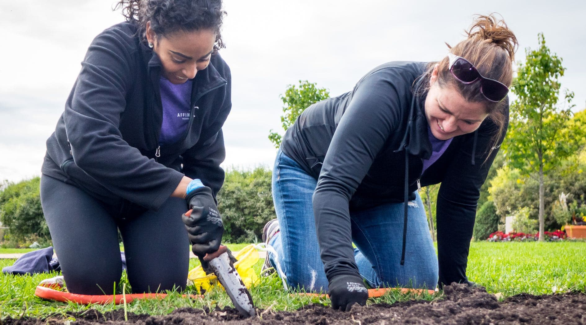 Two Affinity Plus employees gardening outdoors