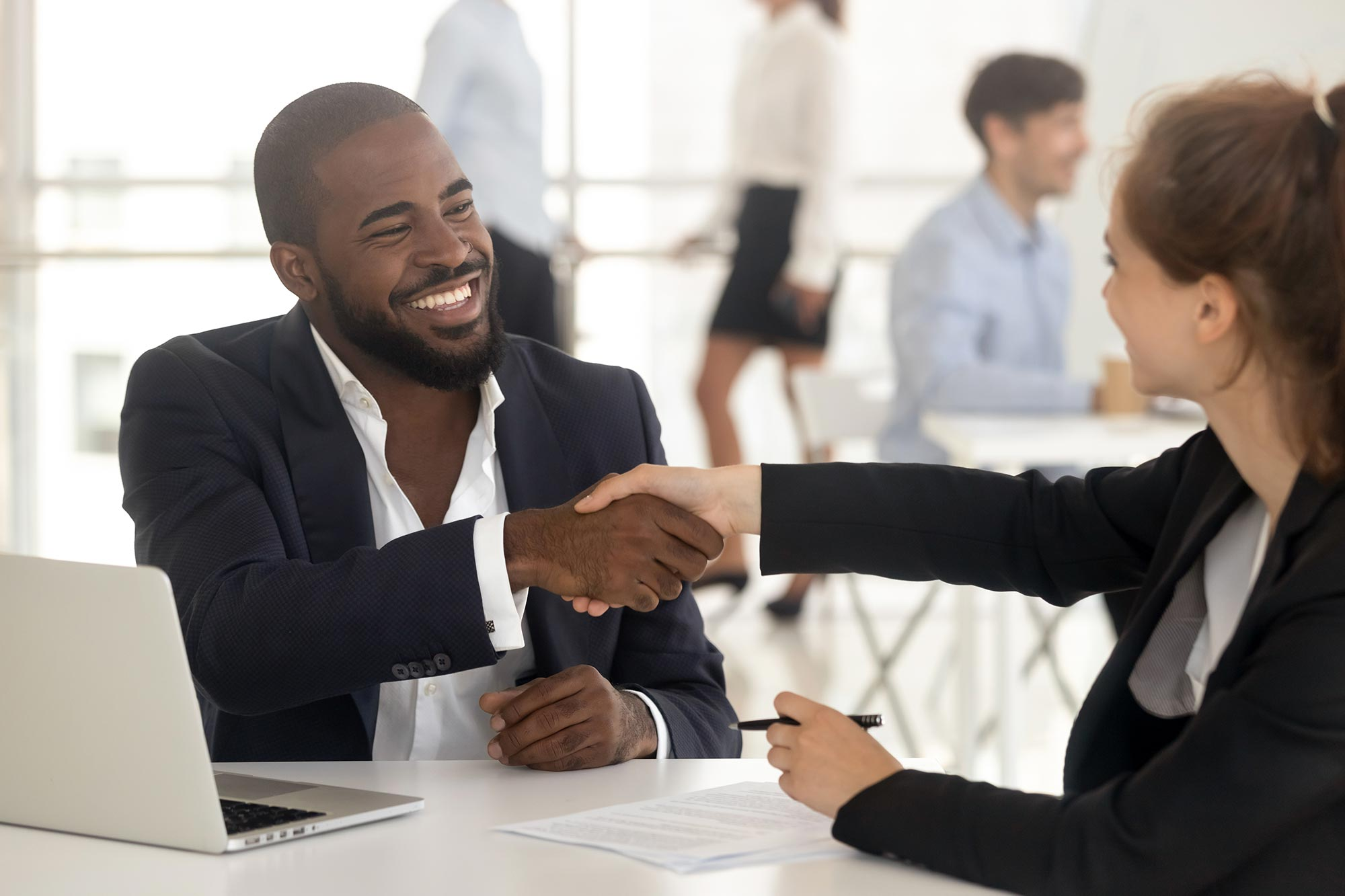 A man and woman shaking hands at a meeting in an office setting