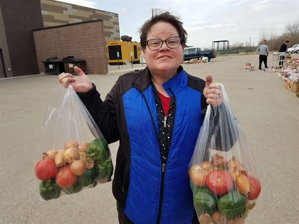 A person holding a bag of fresh vegetables in each hand