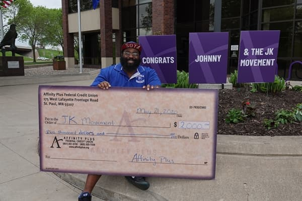 Man holding a check from Affinity Plus to JK Movement for $2,000