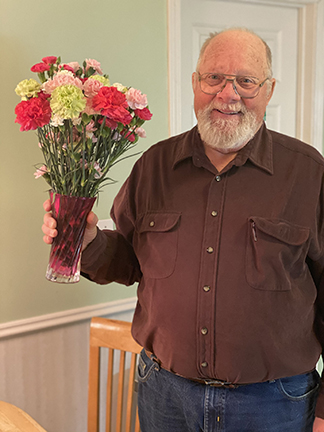 Bearded man wearing glasses and a brown shirt, holding a vase of roses.
