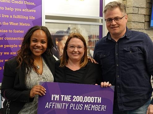three people holding large purple sign