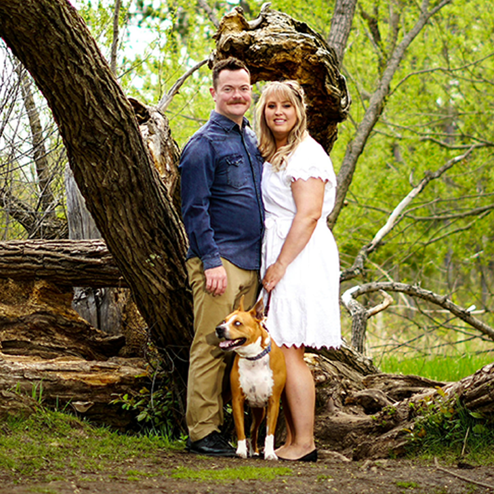 A couple in a wooded area posing with a dog