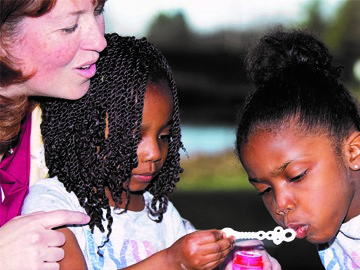 women and two girls blowing bubbles