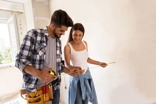 Couple with a measuring tape against a white wall