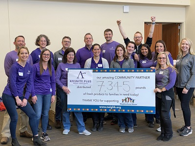 group of people wearing purple shirts holding large check