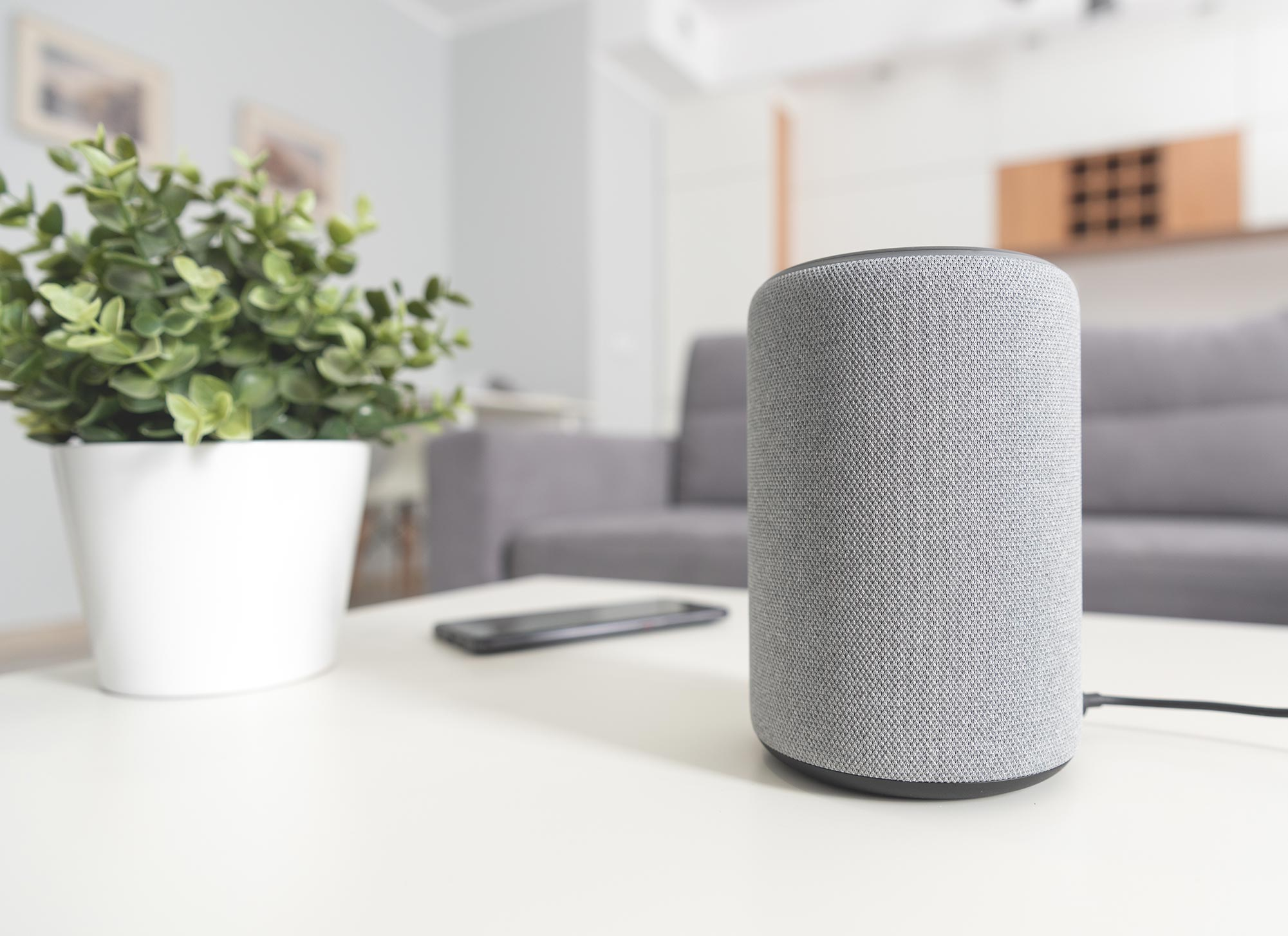 A speaker on a table of a home with a couch blurred in the background