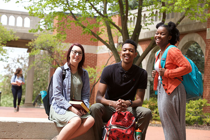 A group of 3 students with backpacks on a college campus